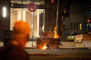A dumpster is lit on fire infront of a Target store in Oakland California on May 30, 2020, over the death of George Floyd, a black man who died after a white policeman kneeled on his neck for several minutes. - Violent protests erupted across the United States late on May 29 over the death of a handcuffed black man in police custody, with murder charges laid against the arresting Minneapolis officer failing to quell boiling anger. (Photo by Josh Edelson / AFP) (Photo by JOSH EDELSON/AFP via Getty Images)