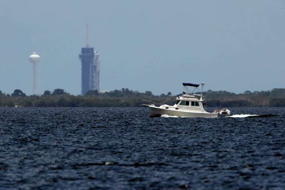 A boat passes the SpaceX Falcon 9, with Dragon crew capsule on top of the rocket Friday, May 29, 2020, at Launch Pad 39-A at the Kennedy Space Center in Cape Canaveral, Fla. Two astronauts will fly on the SpaceX Demo-2 mission to the International Space Station currently scheduled for launch weather permitting on Saturday, May 30. For the first time in nearly a decade, astronauts will blast into orbit aboard an American rocket from American soil, a first for a private company. Photo: Charlie Riedel, AP / Copyright 2020 The Associated Press. All rights reserved.