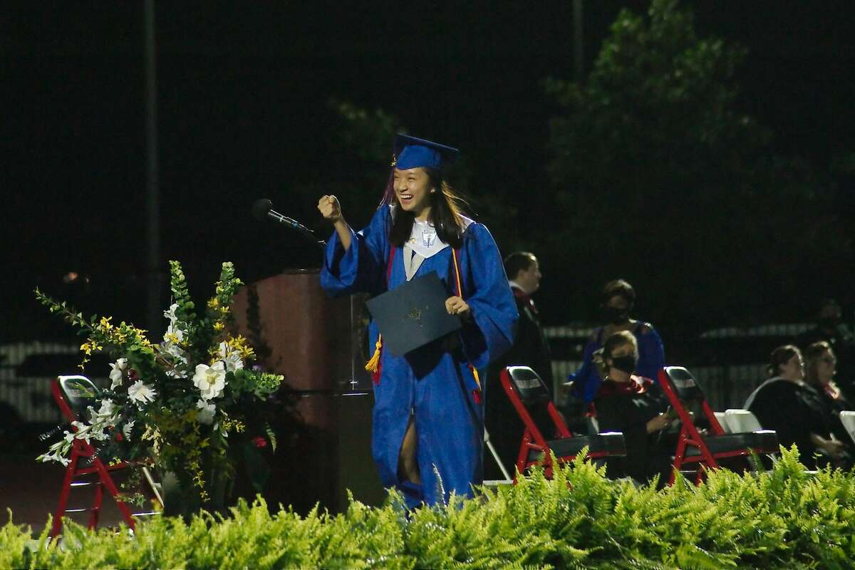Clear Lake High School graduate Kristyn Theriot trades an air fist bump with Principal David Drake as she walks across the stage at CCISD Challenger Columbia Stadium Friday, May 29.