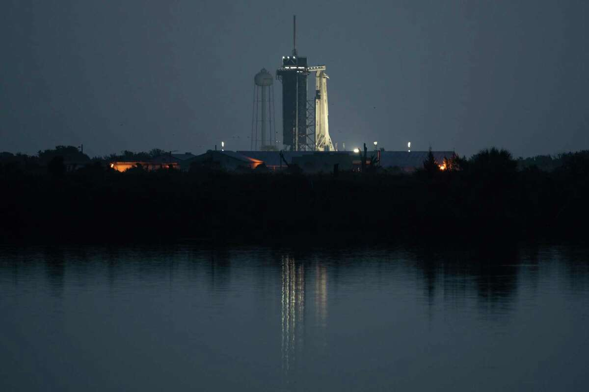 In this image provided by NASA, a SpaceX Falcon 9 rocket, with the company's Dragon crew capsule onboard, is illuminated on the launch pad at Launch Complex 39A as preparations continue for NASA's SpaceX Demo-2 mission, Saturday, May 30, 2020, at the Kennedy Space Center in Cape Canaveral, Fla. Despite more storms in the forecast, SpaceX pressed ahead Saturday in its historic attempt to launch astronauts for NASA, a first by a private company. (Joel Kowsky/NASA via AP)
