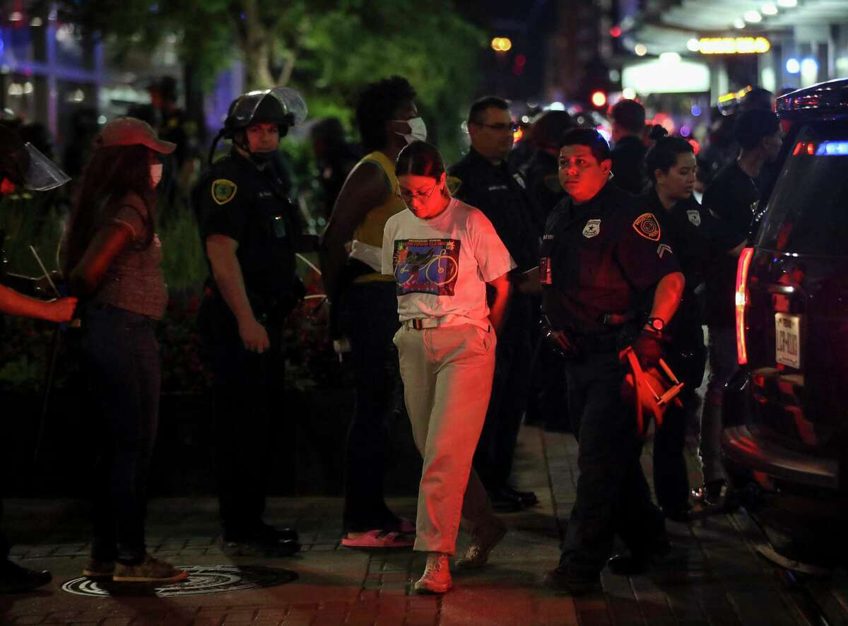 People are detained after authorities gathered a large group of people into a space along Main Street on Friday, May 29, 2020, in Houston. Tensions erupted following a downtown rally over George Floyd's death earlier in the afternoon.