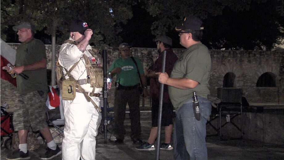 Men stand in front of the Alamo with guns on Saturday morning. Photo: 21 Pro Video