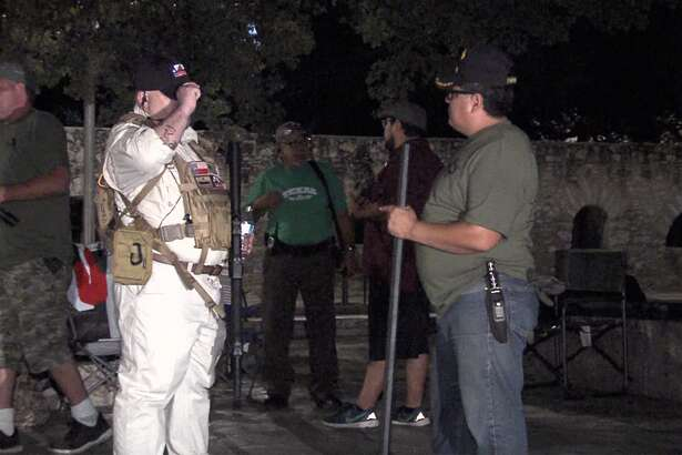 Men stand in front of the Alamo with guns on Saturday morning.