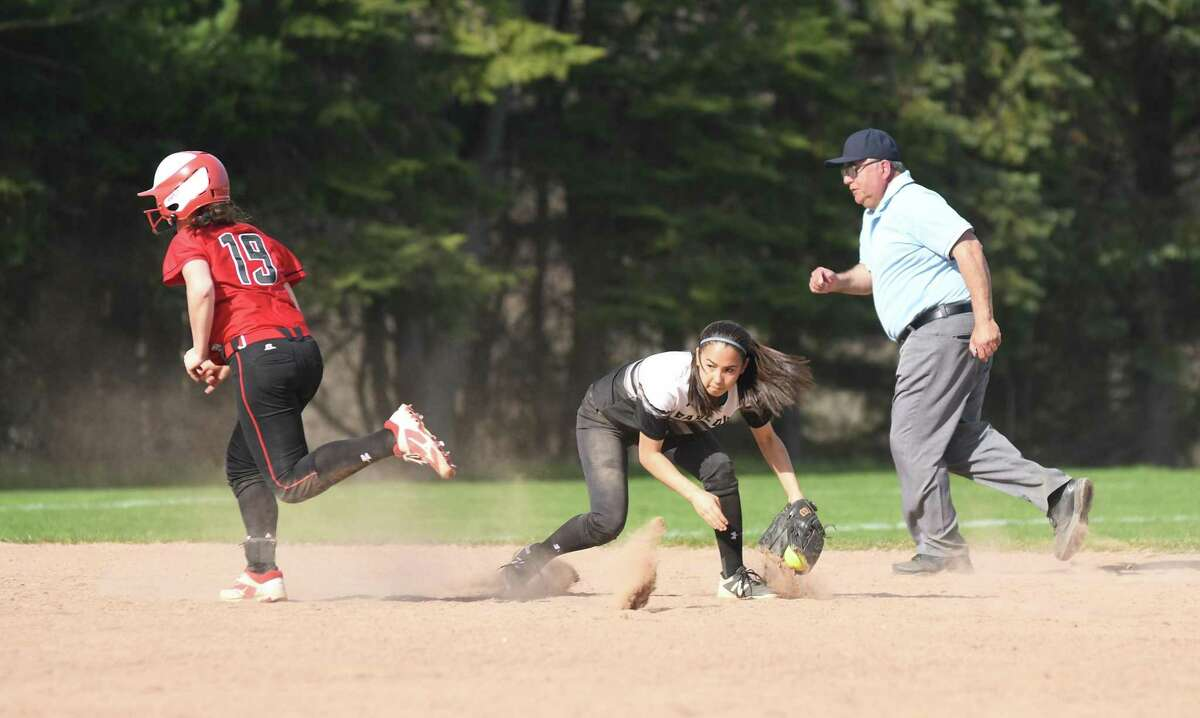 Barlow's Abby Ota, center, fields the ball as Masuk's Katie Welch sprints to third base during their SWC softball game in Monroe in 2018.