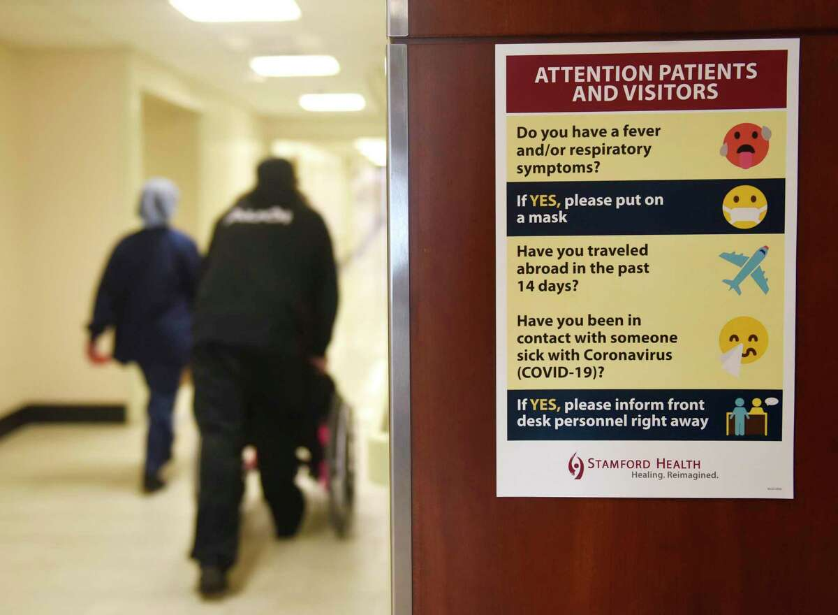 Signs encourage patients and visitors to wear masks at Stamford Hospital in Stamford, Conn. Thursday, March 4, 2020.