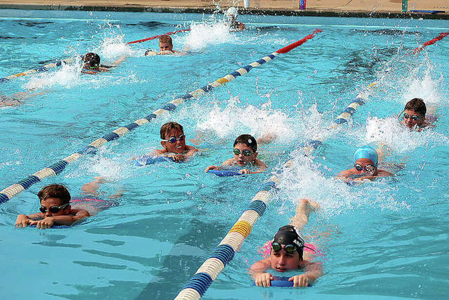 Members of the Summers Port pool swim team use kick boards to work on leg strength during a 2019 practice. The Southwestern Illinois Swim Association, of which Summers port is a member, voted Saturday not to hold its 2020 summer season because of the COVID-19 pandemic. The Summers Port board will likely decide this week whether or not to open. According to the Illinois Department of Public Health, the earliest pools could open is June 26. Photo: Pete Hayes File | The Telegraph