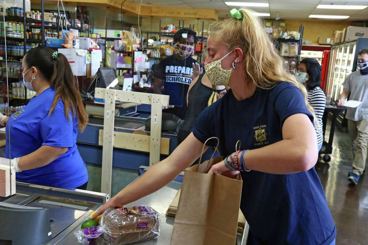 Gigi Speer helps with the bagging at checkout on Saturday, May 23, 2020, at The Pantry in Fairfield, Conn.