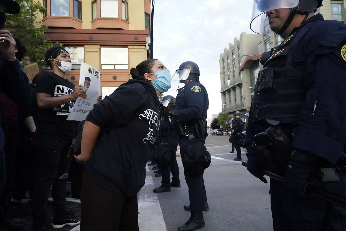 Protestors confront a police line protecting the Oakland Police Department building on 7th St. and Broadway as they protest the killing of George Floyd by police in Minneapolis on Friday, May 29, 2020, in Oakland, Calif.