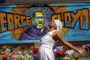 File photo showing a woman reacting to a memorial for George Floyd on May 30, 2020, after protests nationwide calling for justice for Floyd, who died while in custody of the Minneapolis police, on May 25, 2020 in Minneapolis, Minn. (Photo by Kerem Yucel / AFP via Getty Images)