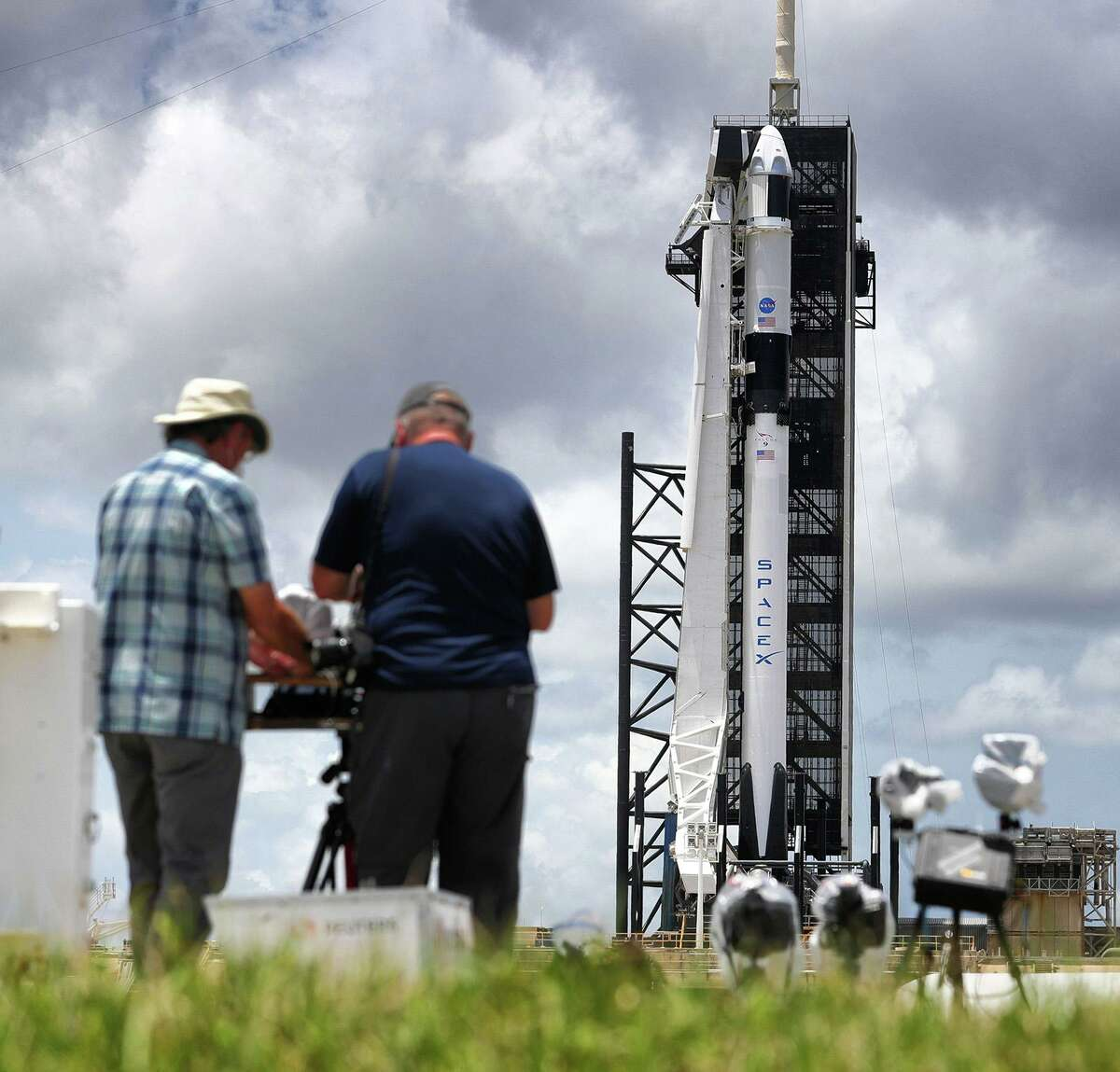 News photographers set up remote cameras as the Crew Dragon capsule sits on top of the SpaceX Falcon 9 rocket at Launch Complex 39-A at Kennedy Space Center, Fla., Friday, May 29, 2020. The second launch attempt of the Demo-2 mission is scheduled for Saturday at 3:22pm. (Joe Burbank/Orlando Sentinel/TNS)