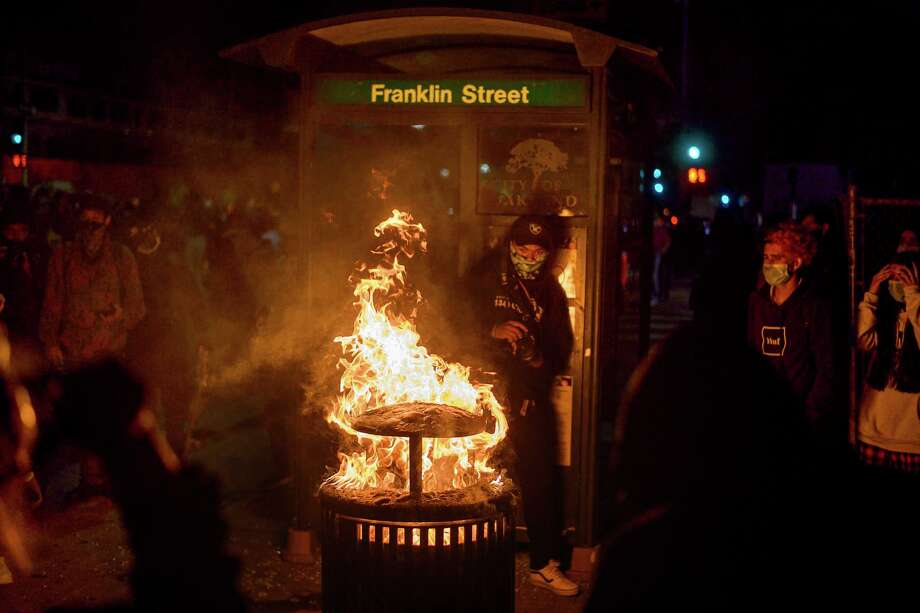 In this May 29, 2020, photo, a fire burns in a trash can as demonstrators protest in Oakland, Calif. against the Monday death of George Floyd, a handcuffed black man in police custody in Minneapolis. Photo: Noah Berger, AP / FR34727 AP