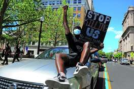 A protestor sits on the hood of a vehicle as he and dozens of others make their way along Main Street in Bridgeport on Saturday. Over 100 people started protesting at Bridgeport Police headquarters before heading to McLevy Green in downtown Bridgeport and then over to the East Side. The protest was one of dozens all over the country after the death of George Floyd in Minneapolis.