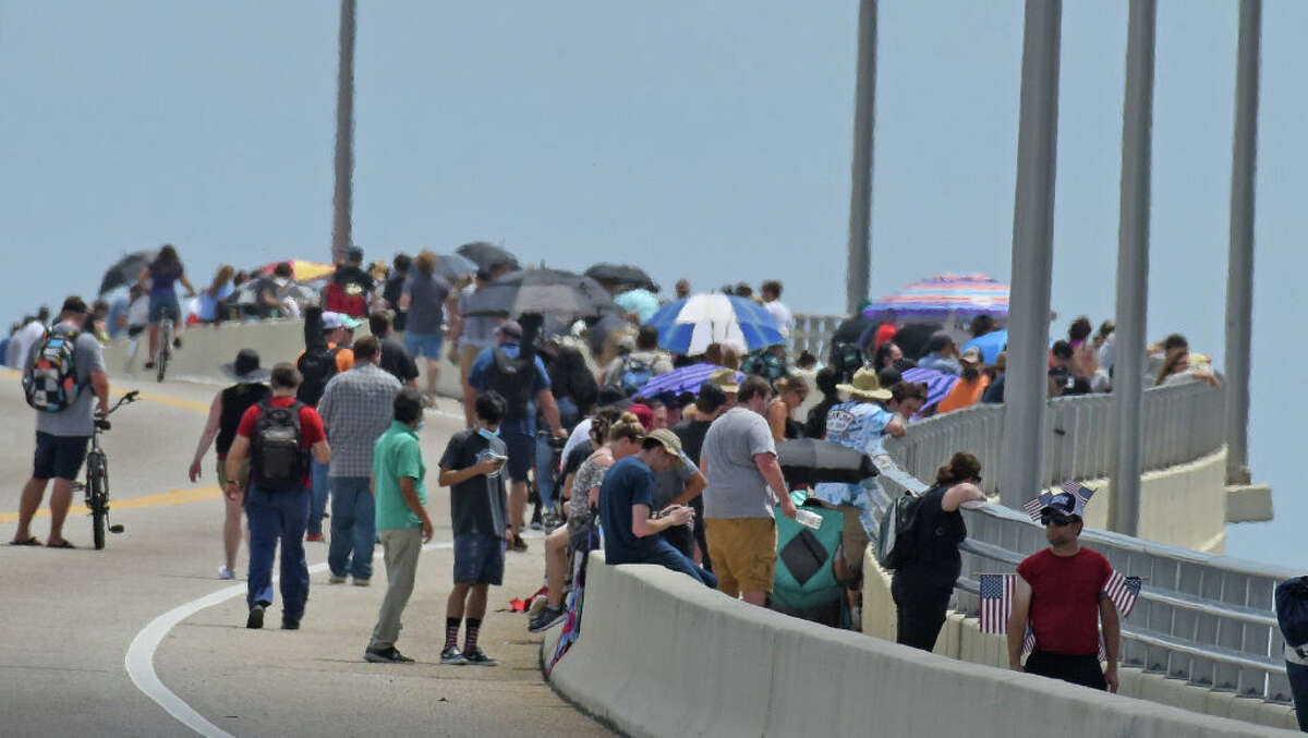 TITUSVILLE, FL - MAY 30: People gather along the A.Max Brewer Causeway ahead of the launch of a SpaceX Falcon 9 rocket from Cape Canaveral, Florida May 30, 2020 in Titusville, Florida. American astronauts Bob Behknen and Doug Hurley are aboard the Crew Dragon capsule on a mission to link up with International Space Station. This is NASA's first crewed launch from U.S. soil since 2011 at the ending of the Space Shuttle program. (Photo by Red Huber/Getty Images)
