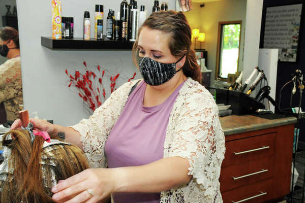 Stylist Julie Valstad works with a client Saturday at My Time Day Spa, 13 Rosa Ave., in Godfrey. The spa is included in the village of Godfrey's recently launched Small Business Community Gift Card program, in which the village subsidizes half of the face value of online-purchased gift cards to be spent at merchants in the Godfrey business district.