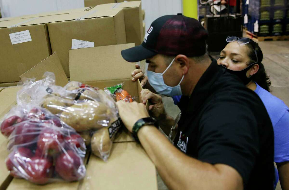 San Antonio Food Bank Warehouse Manager David Carvajal inspects a box of produce from the CRE8AD8/USDA contract, Thursday, May 28, 2020.