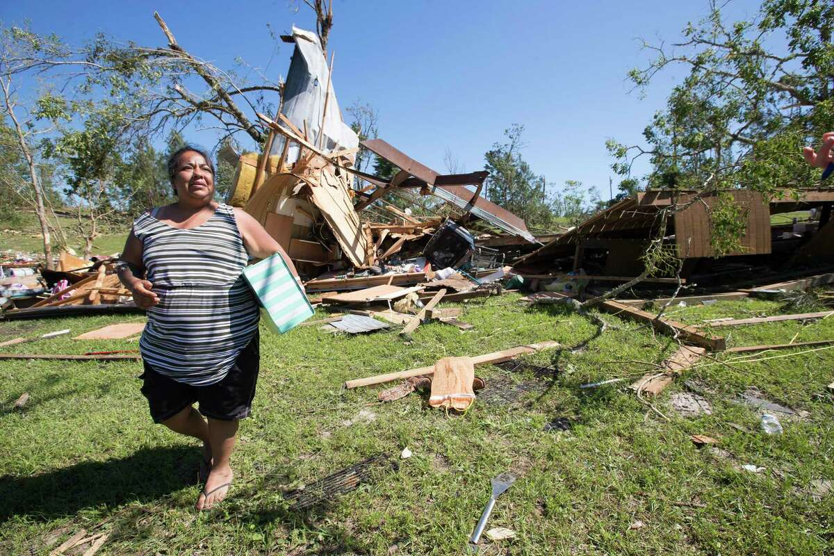 Mayra Jimenez carries a box of her belongings from her destroyed home on Thursday, April 23, 2020, after a tornado ripped through the area in Onalaska, Texas. Several people were killed and up to 30 people were injured Wednesday as a tornado ripped through the small East Texas city, about 85 miles north of Houston.