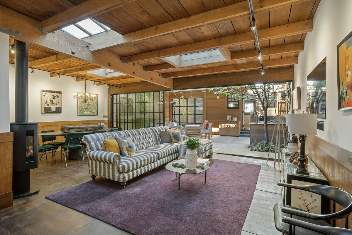 The house itself is 2,345 square feet, but feels even larger thanks to its artful remodeling. A standing gas fireplace and skylights warm the lower level living space. It features custom millwork, natural materials, concrete floors, wood-beamed ceilings, and a wall of glass that opens to the garden patio.