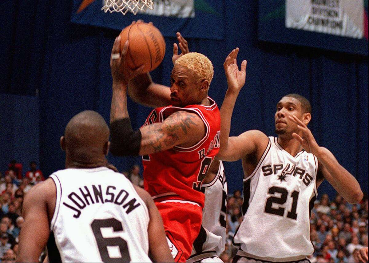 Chicago Bulls' Dennis Rodman, center, grabs a rebound between San Antonio Spurs Avery Johnson (6) and Tim Duncan (21) during the first quarter Saturday, March 14, 1998, at the Alamodome in San Antonio. (AP Photo/Joey Garcia)