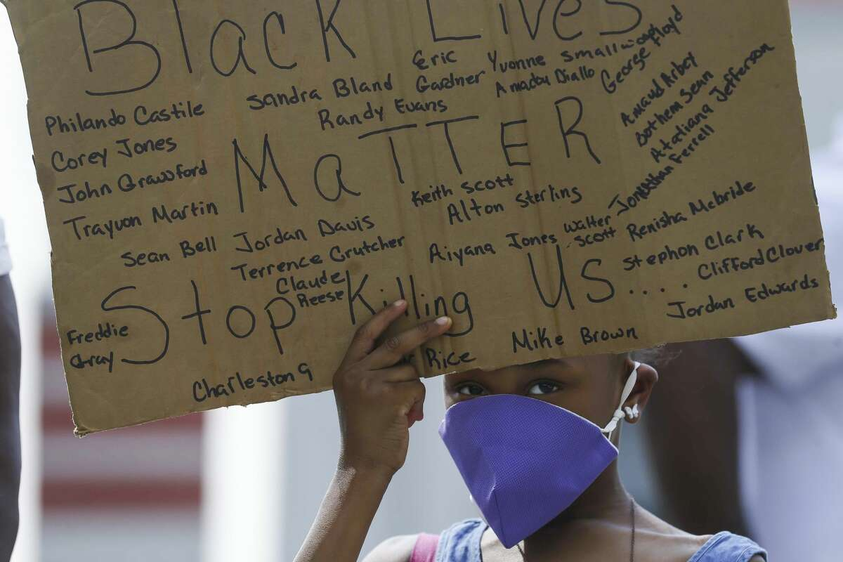 Kailia Allen, 8, holds a sign during a demonstration for Houston native George Floyd, who died in custody of the Minneapolis police earlier this week, during a rally Saturday, May 30, 2020, at Emancipation Park in Houston.