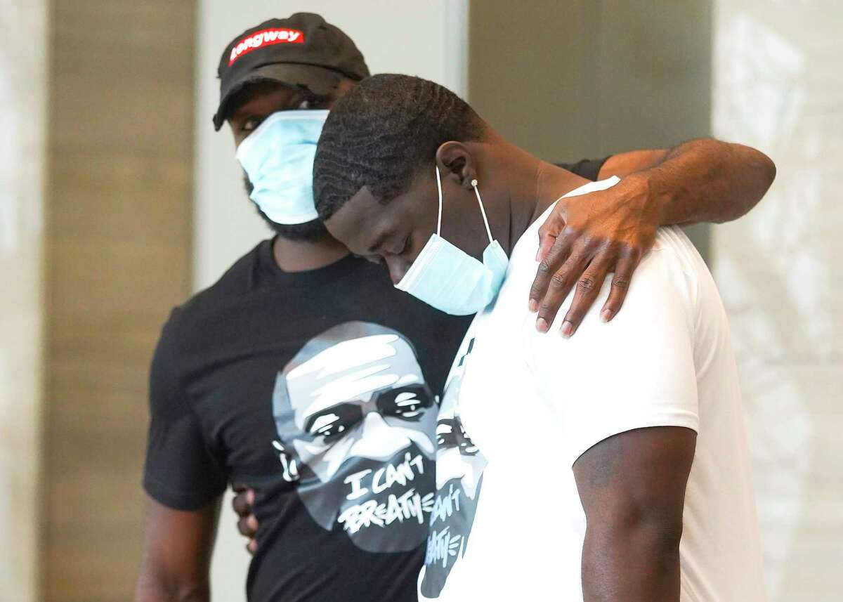 Brandon Williams, right, is comforted by friend Xavier Roberson during a press conference about his uncle hosted by U.S. Congresswoman Sheila Jackson Lee in Houston on Saturday, May 30, 2020.