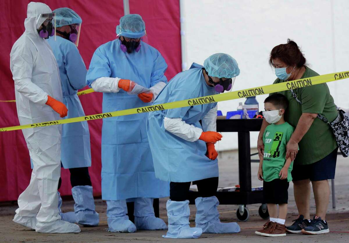 Jerry A. Mann, second from right, stands with his grandmother, Sylvia Rubio, as he prepares to be tested for COVID-19 by the San Antonio Fire Department at a free walk-up test site. There are dozens of free test sites set up throughout the city; to get more information, call 311. More than 60,000 area residents have been tested.