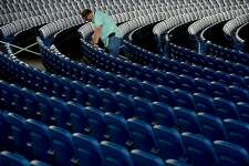 Nederland High School Principal Steven Beagle joins staff in taping off seats and rows as they prepare the seating areas for social distancing before Nederland's graduation at Ford Park Pavilion Friday night. Photo taken Friday, May 29, 2020 Kim Brent/The Enterprise