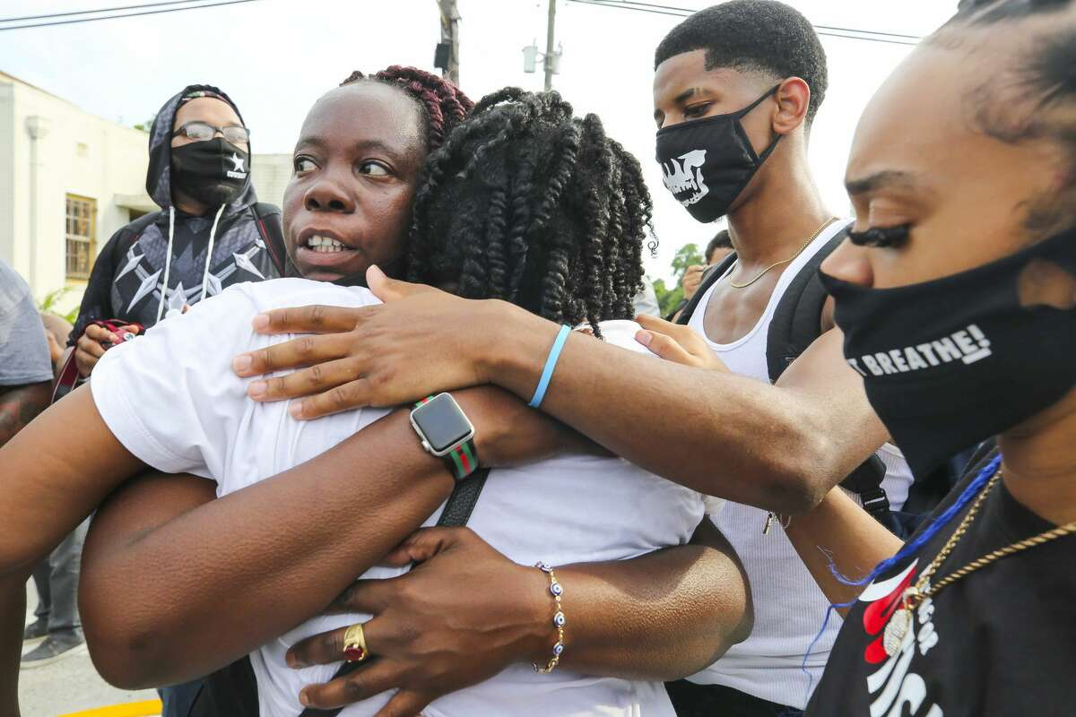 Protestors hug during an ongoing rally for George Floyd, a Houston native who died in custody of the Minneapolis police earlier this week, during ongoing demonstrations Saturday, May 30, 2020 in Houston.