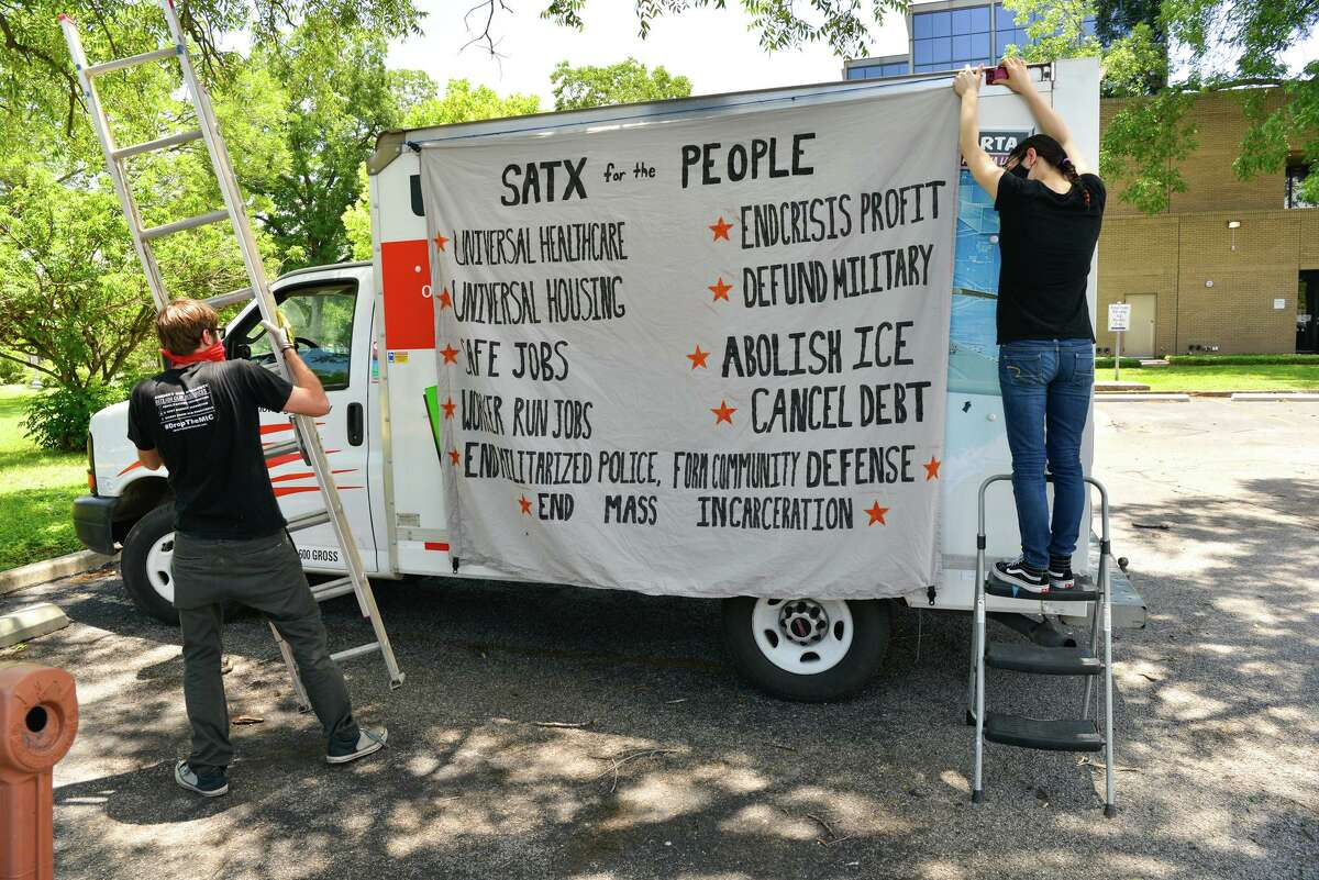 Jake Tucker, left, of the Party for Socialism and Liberation works to place a banner on a truck while an activist who didn't want to be identified helps before a protest by caravan.
