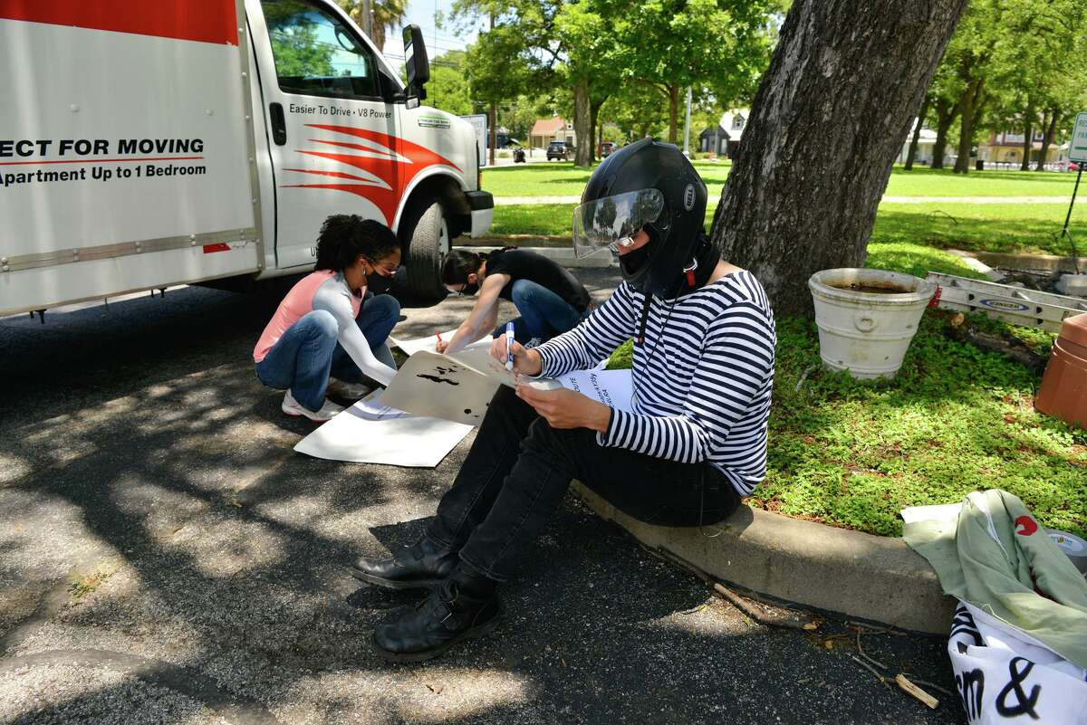 An activist who didn't want to be identified make posters before a car caravan protest Saturday afternoon. They were demanding that the San Antonio Housing Authority and other landlords cancel rent payments.