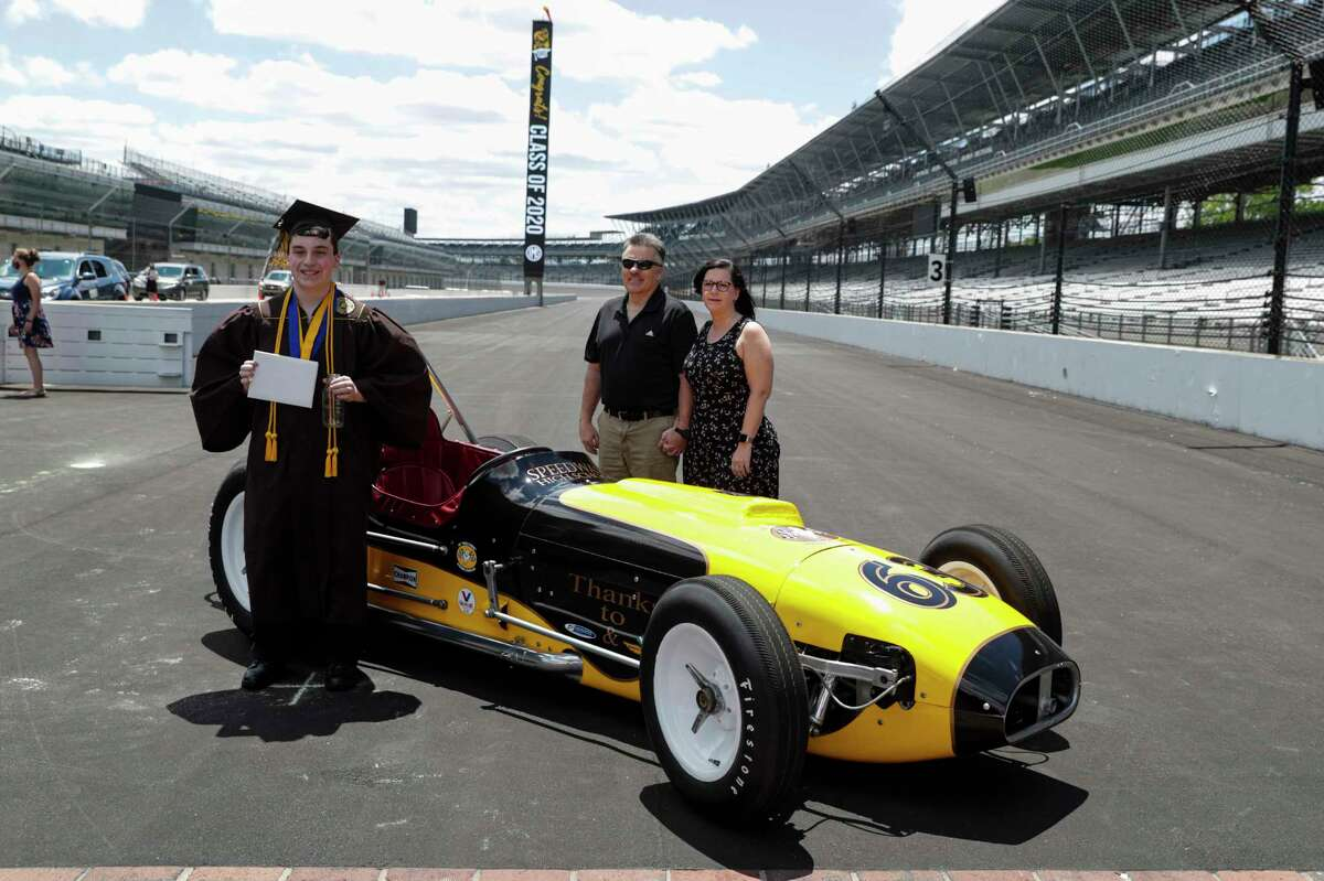 Jacob Foxworthy, left, poses with his parents Ted and Cindy Foxworthy around a vintage race car after he received his Speedway High School diploma during a ceremony at the Indianapolis Motor Speedway in Indianapolis, Saturday, May 30, 2020. When Ted Foxworthy was diagnosed with cancer, he set two goals: Celebrating his youngest child's 18th birthday and seeing him graduate. (AP Photo/Michael Conroy)