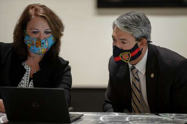 Metro Health Director Dawn Emerick shares the day's COVID-19 case numbers with Mayor Ron Nirenberg during a briefing with city officials.