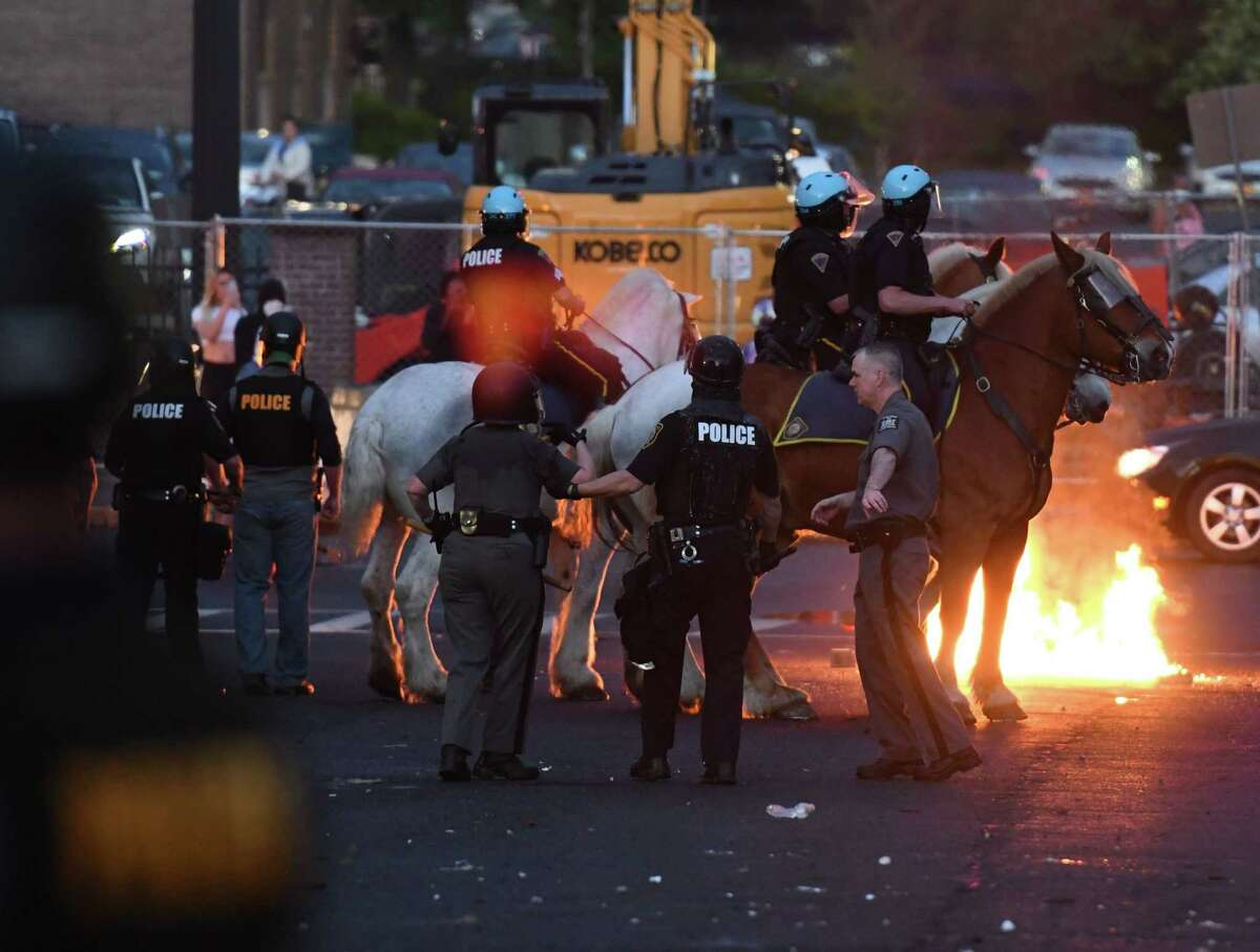 A firebomb is thrown at mounted police as they worked to disperse protesters who gathered outside the Albany Police Department South Station on Saturday night, May, 30, 2020, in Albany, N.Y. The confrontation followed peaceful protests in the city over the killing of George Floyd, an unarmed black man, by police in Minneapolis. (Will Waldron/Times Union)
