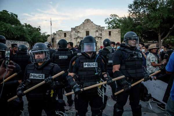 """San Antonio police officers stand at the Alamo last month as people protest  the death of George Floyd. But there have also been unwelcome armed """"defenders"""" of the Alamo. We can't let such fringe groups hijack a full retelling of the Alamo story."""