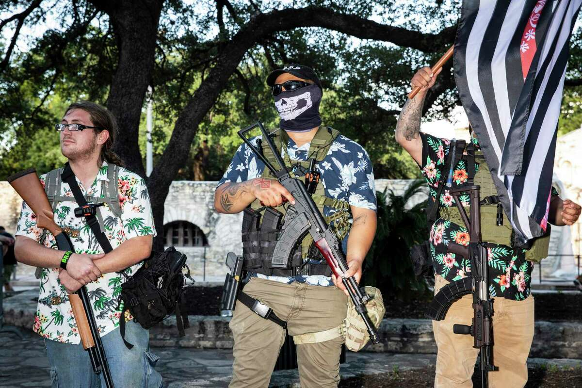 Military-style groups brandished firearms to protect the Cenotaph in front of the Alamo.