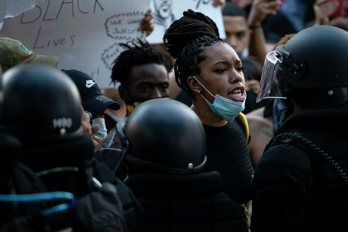 A protestor speaks with police officers during a protest to honor George Floyd on Saturday May 30, 2020.