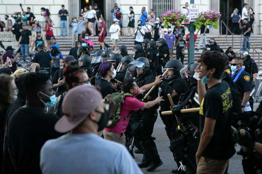 Protestors and police officers clash near Alamo Plaza during a protest to honor George Floyd in downtown in San Antonio, Texas, on May 30, 2020. Floyd died in the custody of the Minneapolis Police Department and his death has sparked protests across the country. Photo: Josie Norris, The San Antonio Express-News / Staff Photographer / **MANDATORY CREDIT FOR PHOTOG AND SAN ANTONIO EXPRESS-NEWS/NO SALES/MAGS OUT/TV