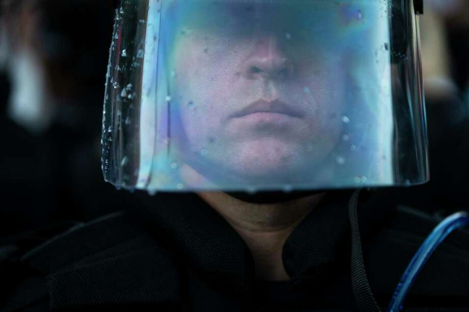Water droplets form on the face shield of a police officer during a protest to honor George Floyd in downtown in San Antonio, Texas, on May 30, 2020. Floyd died in the custody of the Minneapolis Police Department and his death has sparked protests across the country. Photo: Josie Norris, The San Antonio Express-News / Staff Photographer / **MANDATORY CREDIT FOR PHOTOG AND SAN ANTONIO EXPRESS-NEWS/NO SALES/MAGS OUT/TV