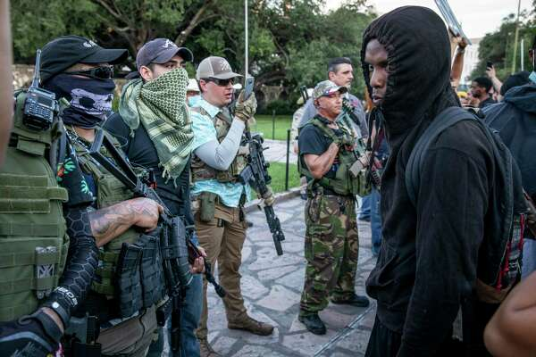 Protestors and military-style groups confronted each other in front of the Alamo.
