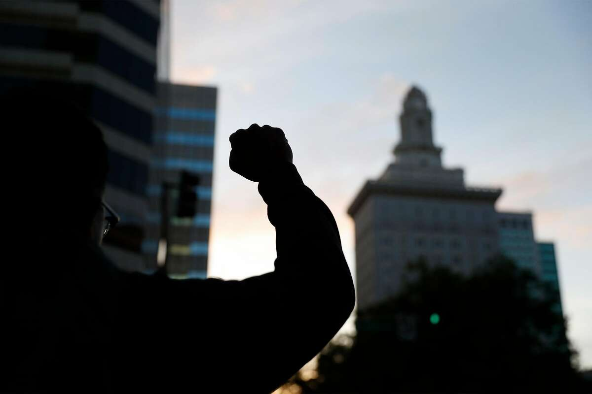 A man raises his fist at 14th and Broadway during a protest in Oakland on May 30, 2020.