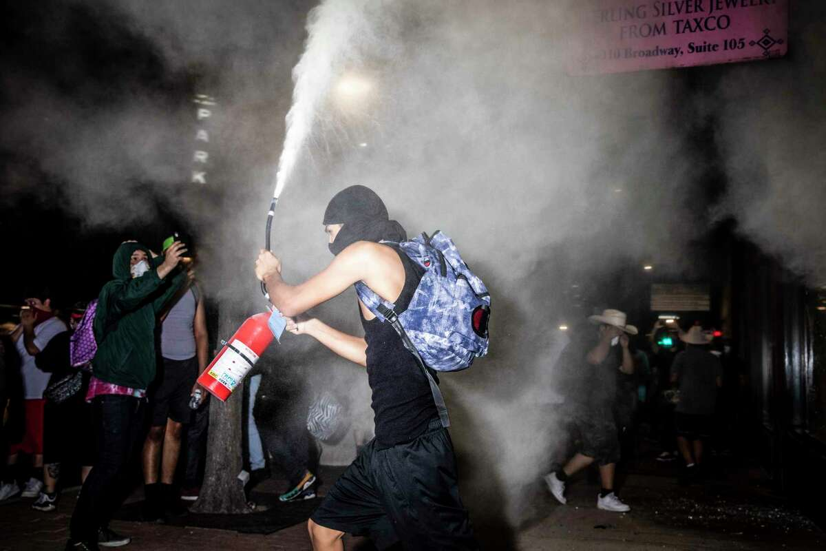A protestor lets off a fire extinguisher in downtown San Antonio, Texas, U.S. on Saturday, May 30, 2020. People took to the streets of San Antonio to protest the killing of George Floyd in Minnesota while he was in police custody. Looting took place in downtown Houston street as police fired tear gas and pepper balls at protestors as they looted stores.