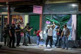 Looters are shot point blank with pepper balls by San Antonio Police Officers on Houston street after they looted Mar Imports jewelry store in downtown San Antonio, Texas, U.S. on Saturday, May 30, 2020. People took to the streets of San Antonio to protest the killing of George Floyd in Minnesota while he was in police custody. Looting took place in downtown Houston street as police fired tear gas and pepper balls at protestors as they looted stores.