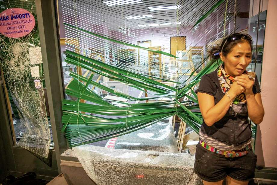 A woman stands outside Mar Imports jewelry store after it was looted. Photo: Matthew Busch, Contributor / For The San Antonio Express-News / **MANDATORY CREDIT FOR PHOTOG AND SAN ANTONIO EXPRESS-NEWS/NO SALES/MAGS OUT/TV