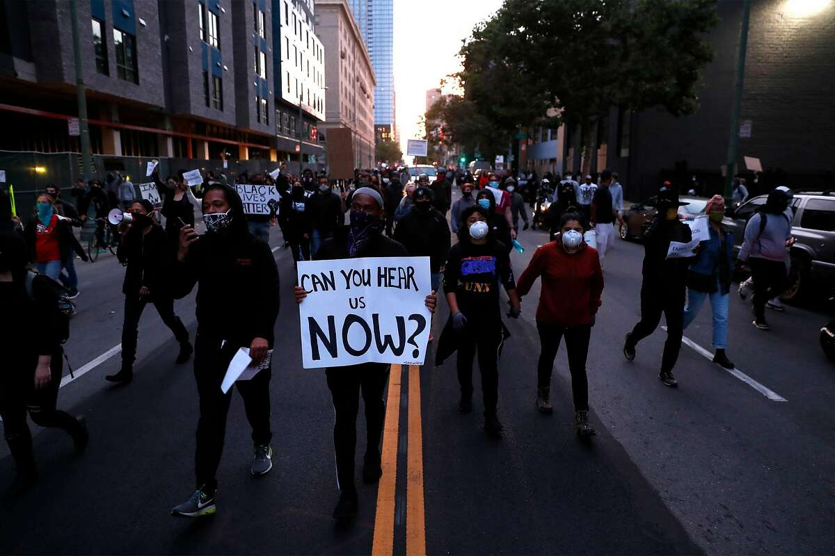 People march on 14th Street during protest, sparked by the death of George Floyd, in Oakland, Calif., on Saturday, May 30, 2020.