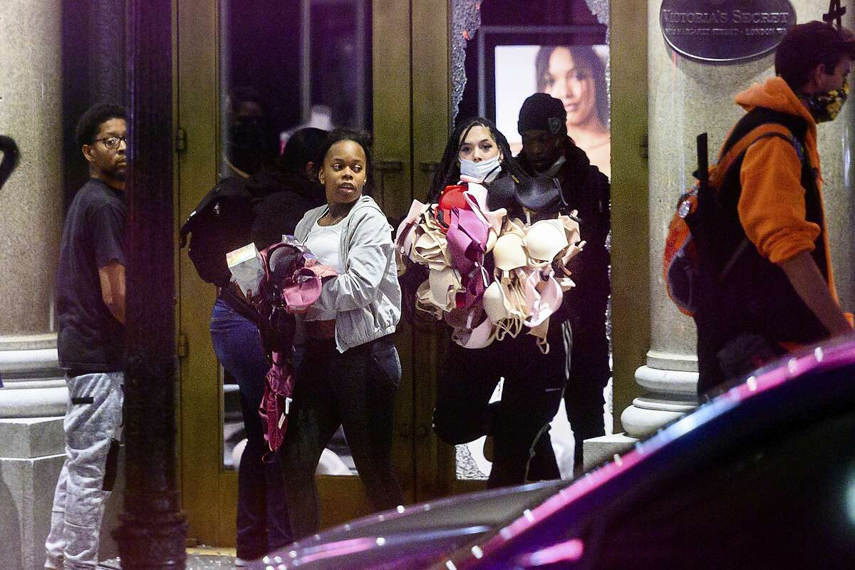 Women carry merchandise from a Union Square Victoria's Secret store in San Francisco on Saturday, May 30, 2020. Widespread vandalizing occurred at stores throughout San Francisco following the death of George Floyd, a handcuffed black man in police custody in Minneapolis.