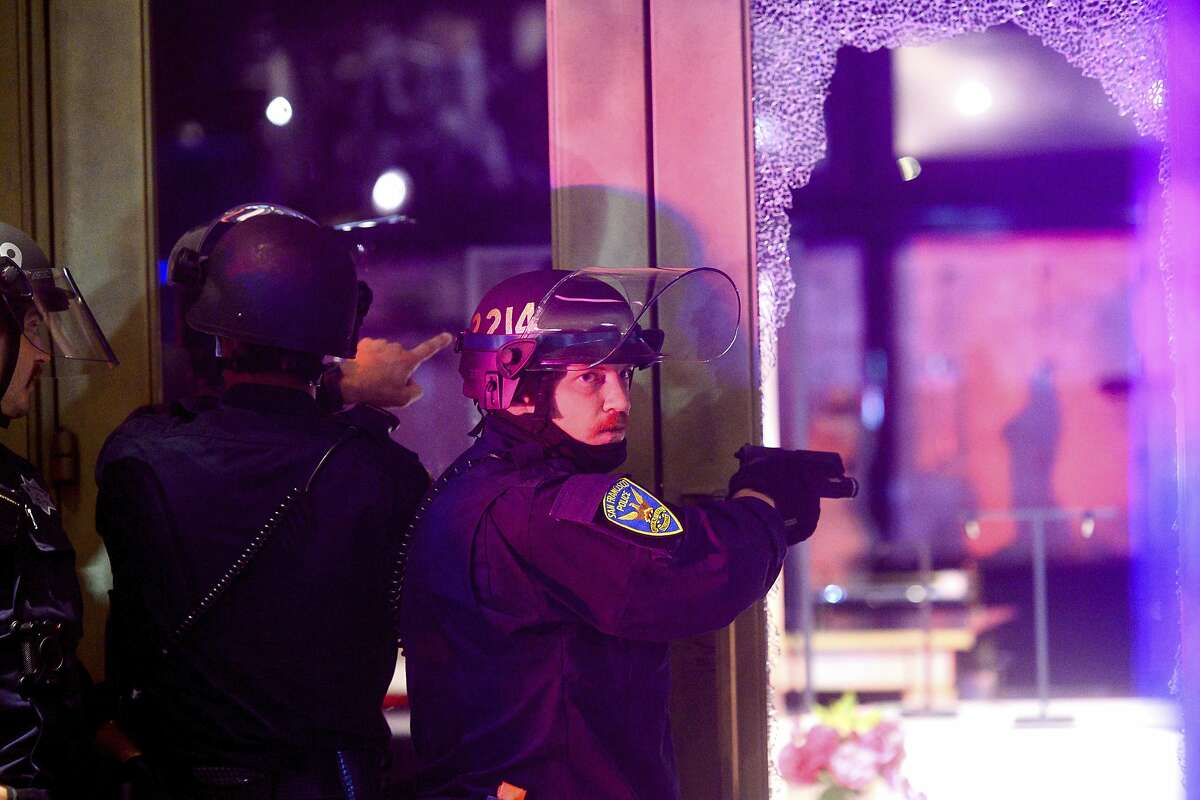 A police officer aims his weapon while clearing a vandalized Victoria's Secret store in San Francisco on Saturday, May 30, 2020. Widespread vandalizing occurred at stores throughout San Francisco following the death of George Floyd, a handcuffed black man in police custody in Minneapolis. (AP Photo/Noah Berger)