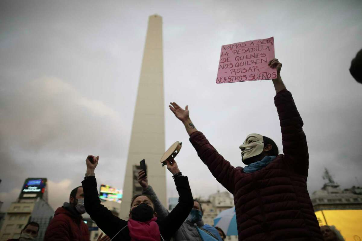 People gather round the iconic Obelisk monument in a protest demanding an end to the government-ordered lockdown put in place help curb the spread of the new coronavirus, in Buenos Aires, Argentina, Saturday, May 30, 2020.