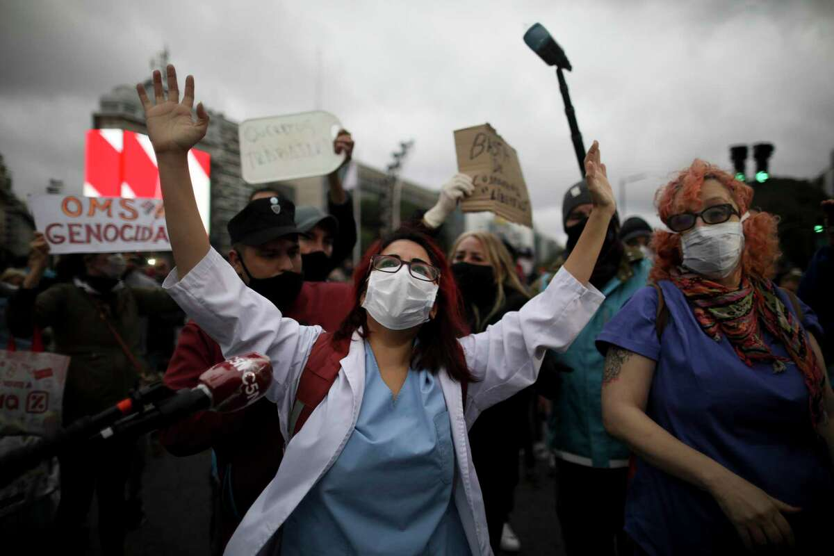 Doctors, front, demonstrate in favor of the government-ordered lockdown to help curb the spread of the new coronavirus while dueling protesters demand an end to the lockdown, in Buenos Aires, Argentina, Saturday, May 30, 2020.