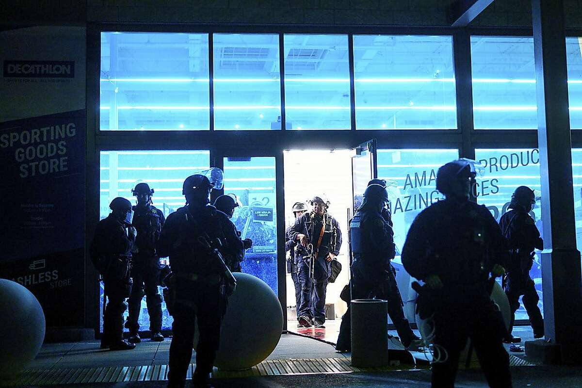 Police officers leave a vandalized Decathlon sporting goods store in Emeryville, Calif., on Saturday, May 30, 2020. Widespread vandalizing occurred at stores throughout San Francisco and Emeryville following the death of George Floyd, a handcuffed black man in police custody in Minneapolis. (AP Photo/Noah Berger)