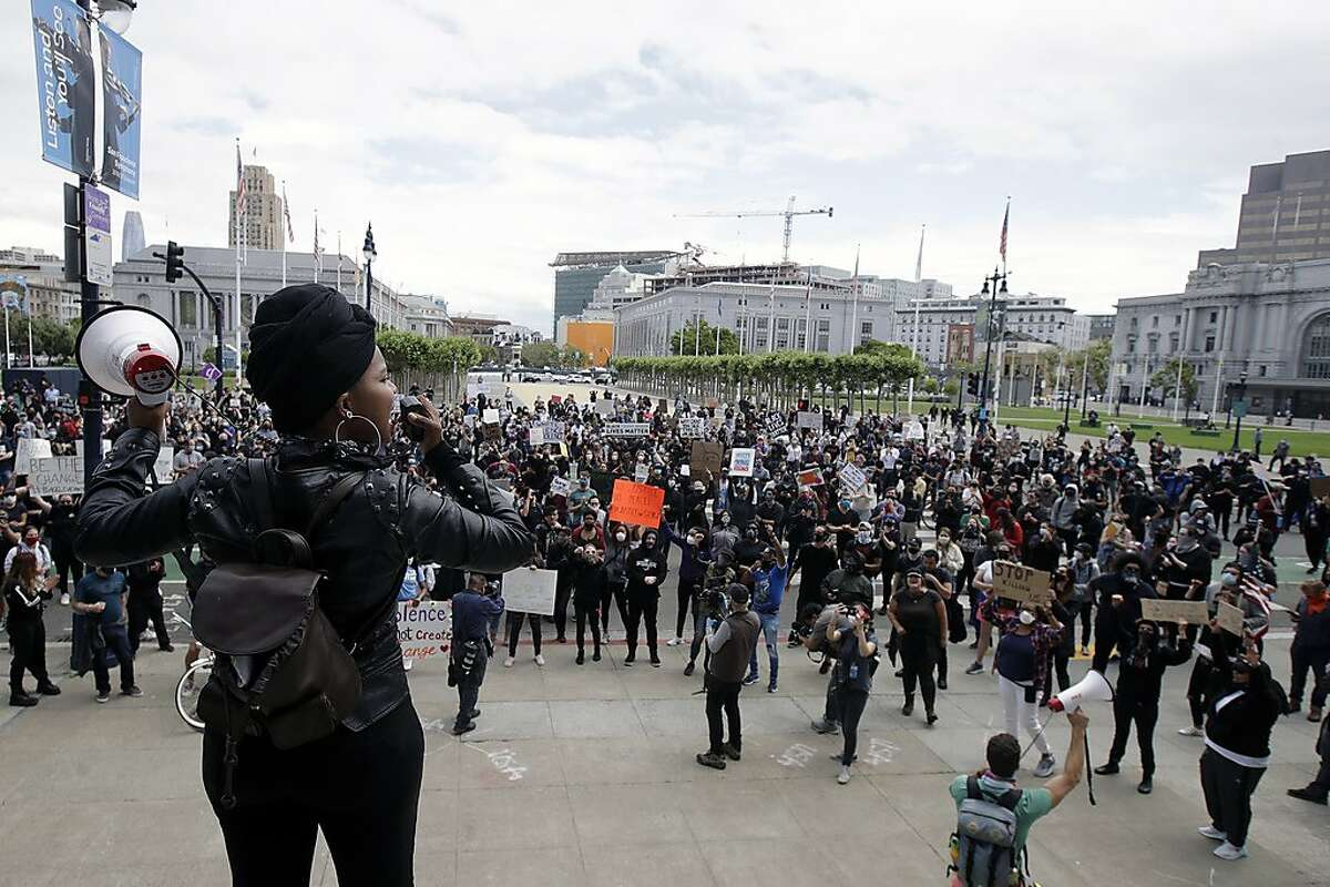 Raiah Sinn, foreground, speaks at a protest over the Memorial Day death of George Floyd, a handcuffed black man in police custody in Minneapolis, in San Francisco, Saturday, May 30, 2020.