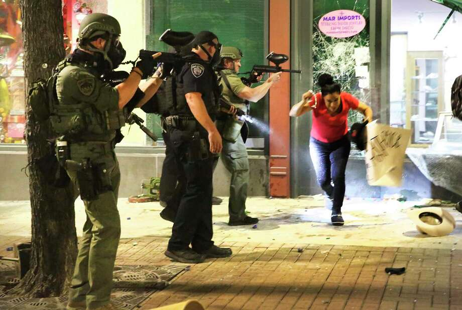 A woman ducks down to avoid police as she leaves a looted store. Photo: Bob Owen, Staff-photographer / San Antonio Express-News / ©2020 San Antonio Express-News